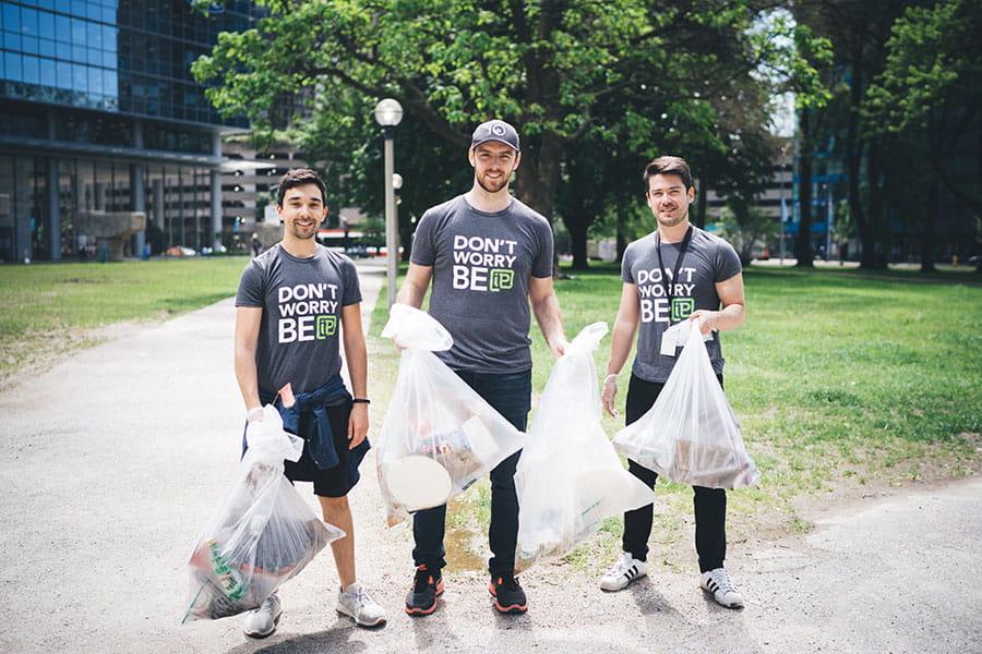 3 men picking up garbage