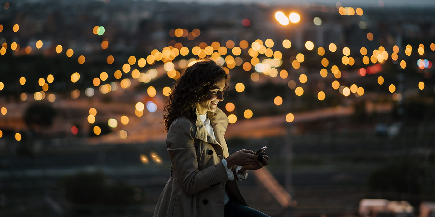 woman on phone in city with lights