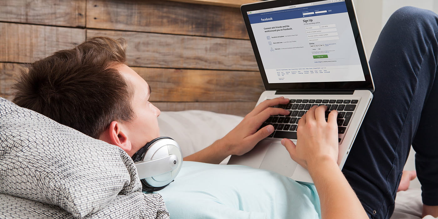 Man reclining and looking at Facebook on laptop