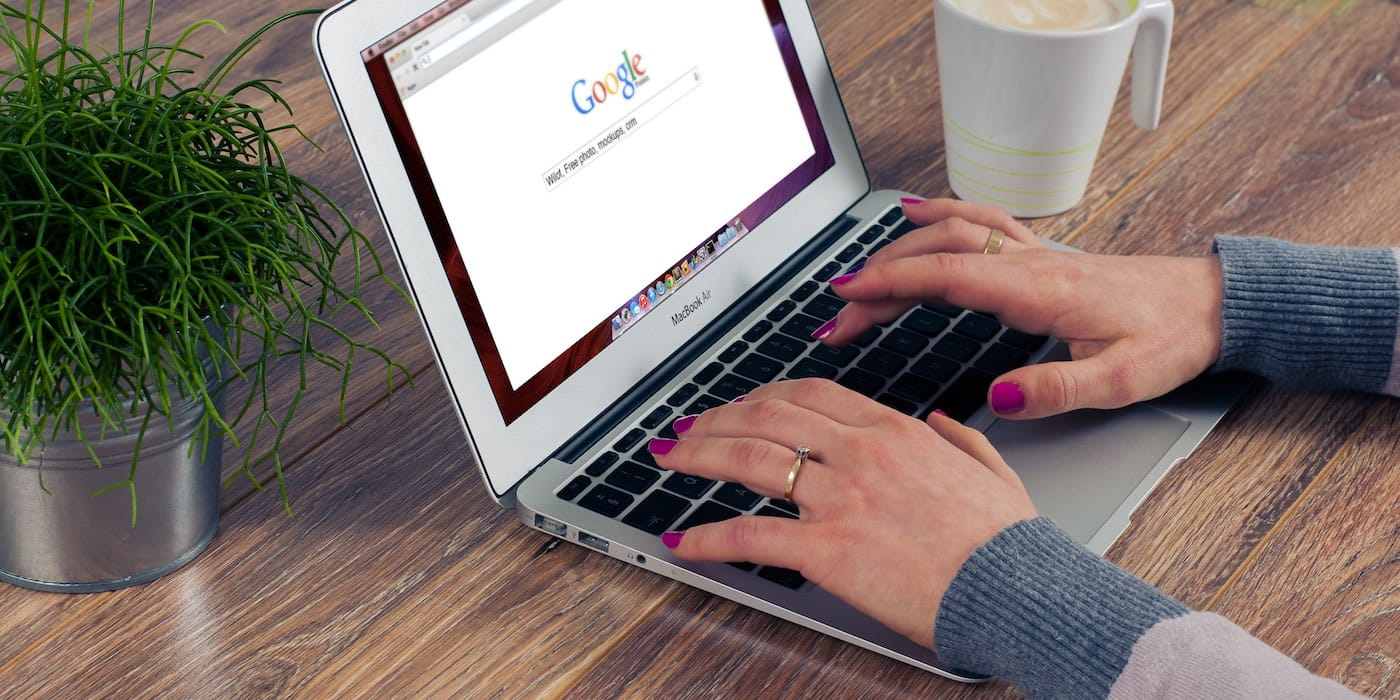 Hands typing on a laptop into a Google search webpage