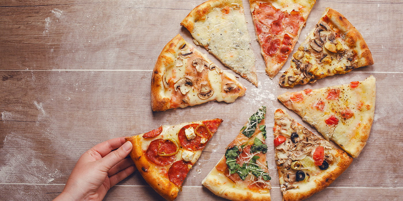 multiple pieces of pizza on a wooden board