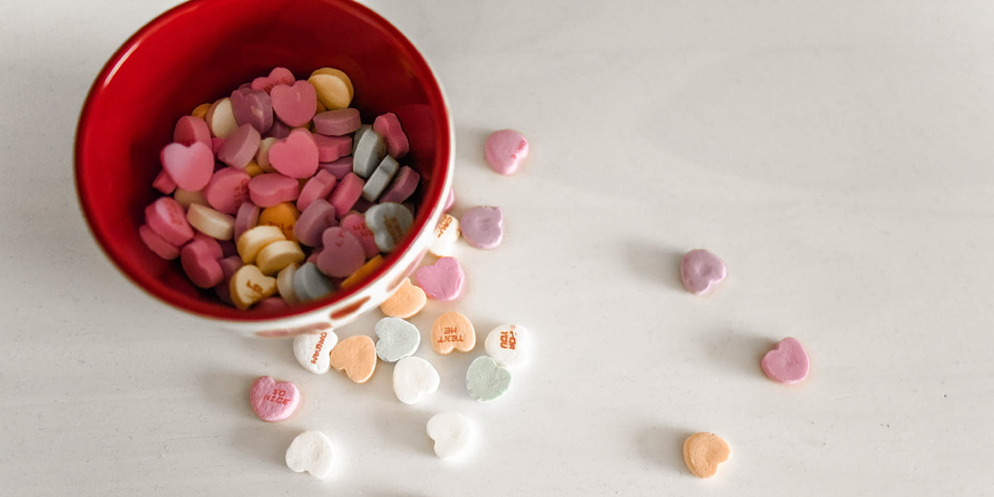 Bowl of conversation hearts with some spilled on a countertop